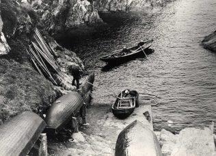 The island pier with naomhóga (canoes), 1940s   Ionad an Bhlascaoid