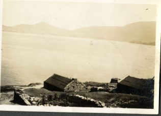 View over the island village, with felt-roofed houses, & the mainland in background. | Ionad an Bhlascaoid
