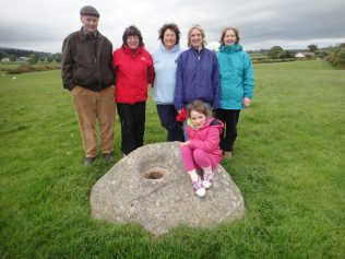 A historical bullaun stone and volunteers | Roundwood Tidy Towns