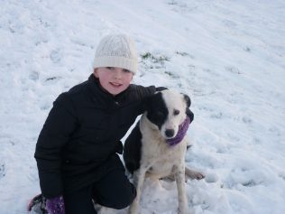 Boy with dog enjoying the snow   Askanagap Community Development Association